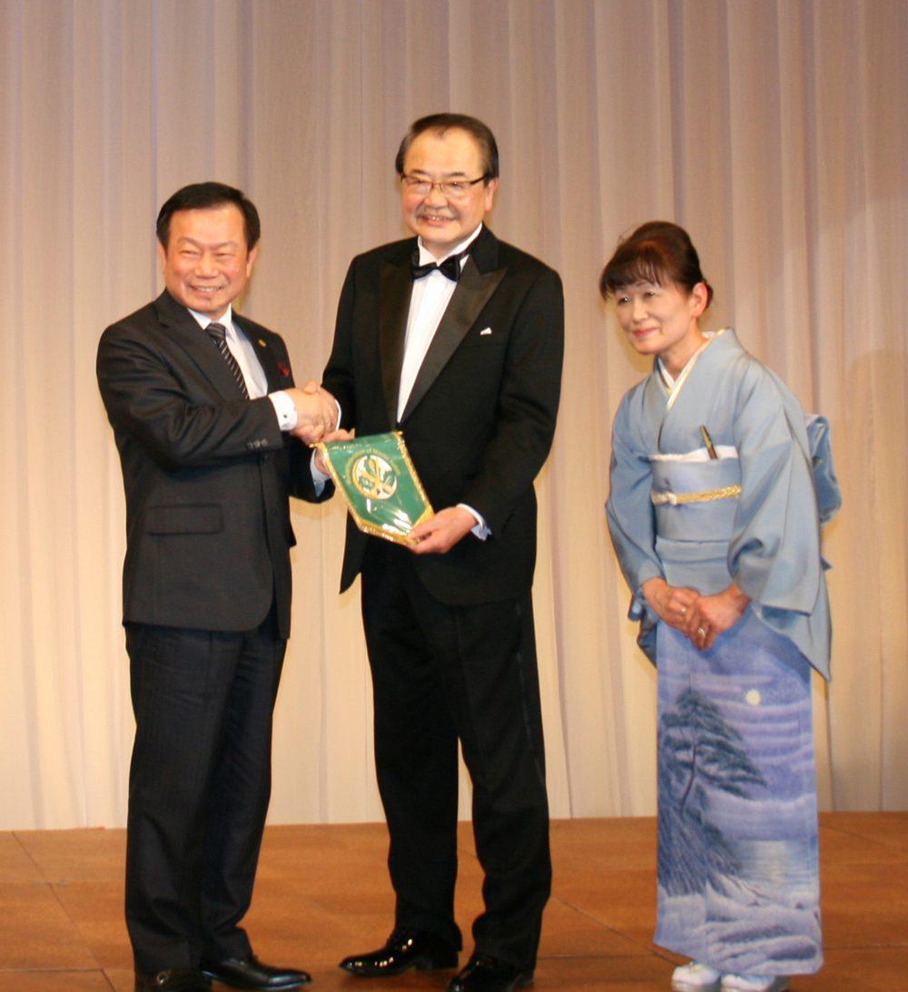 現世界連盟ホー・会長(左)から記念のペナントを贈呈される井場幸男氏(中央)と夫人