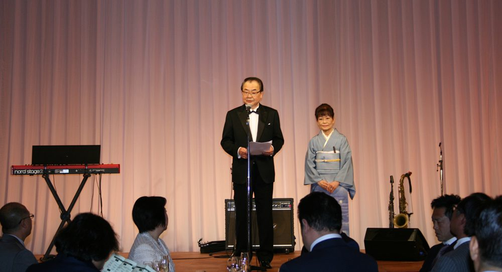 テーラー井場100周年パーティーであいさつする井場幸男氏と里美夫人